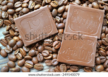 Piece of chocolate on coffee beans on wooden table - stock photo