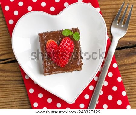Piece of creamy chocolate cake on heart shaped plate, topped with heart shaped strawberry - stock photo