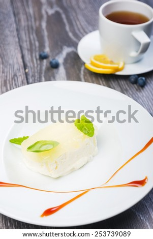 piece of Creamy vanilla ice cream with jelly and mint leaves on a white plate on a wooden table with decor and tea - stock photo