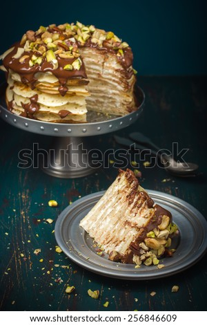 piece of crepe cake with custard cream and chocolate topping and nuts - stock photo