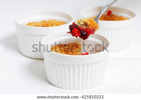 Piece of crumble with raspberries, gooseberries, blackberries and cinnamon on fork. English dessert in a white ceramic mold for baking on white wooden table. Selective focus. - stock photo