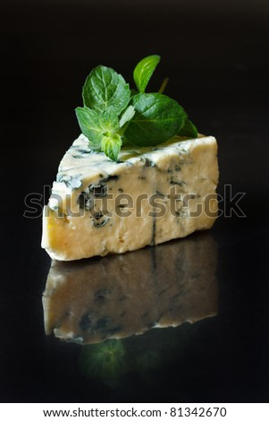 Piece of delicious blue cheese with mint on a black. - stock photo