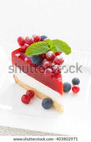 piece of delicious cheesecake with berry jelly on a white plate, top view, vertical - stock photo