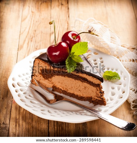 Piece of delicious chocolate mousse cake with cherries and mint on old wooden background. Selective focus. retro style toned.