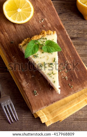 Piece of delicious homemade lemon cheesecake with mint on rustic wooden background close up - stock photo