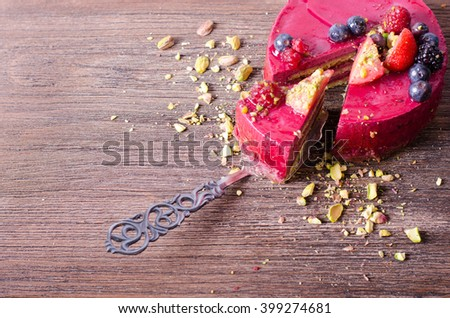Piece of delicious raspberry cake with fresh strawberries, raspberries, blueberry, currants and pistachios on shovel, wooden background. Free space for your text. - stock photo