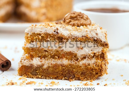Piece of delicious treat carrot cake sweet dessert with pastry cream, walnut, cinnamon and coffee on white background - stock photo