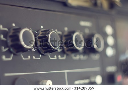 Piece of electrical audio equipment with knobs. Old retro amplifier with selective focus - stock photo