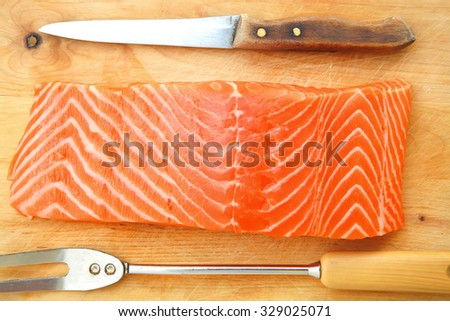 piece of fresh raw salmon on wooden tray isolated on white background - stock photo