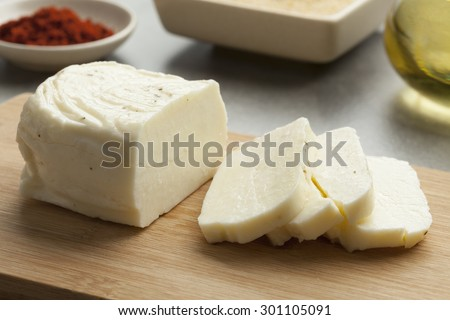 Piece of fresh sliced halloumi on a cutting board - stock photo
