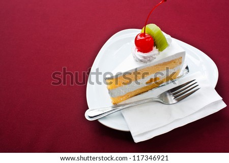 Piece of fruit cake on red tablecloth. - stock photo