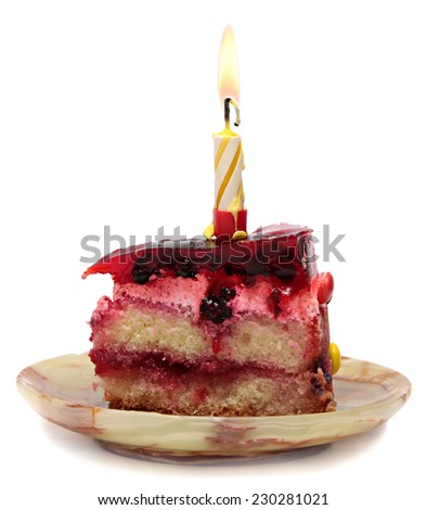 Piece of fruit cake with one burning candle isolated on white background.