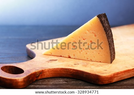 Piece of Gruyere cheese on wooden cutting board against nice dark background - stock photo