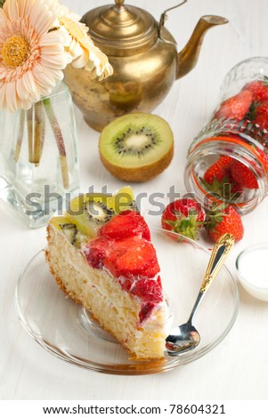 Piece of homemade fruit cake with strawberries and kiwi, old teapot and flowers on white wooden table
