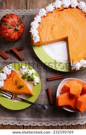 Piece of homemade pumpkin pie on plate on sackcloth background - stock photo