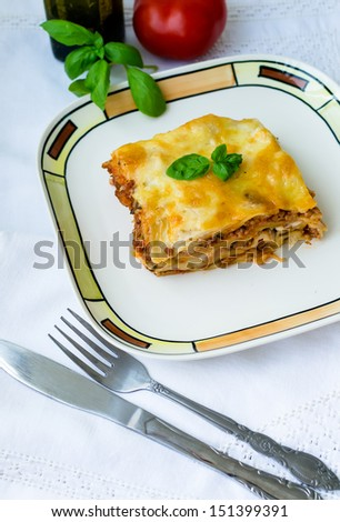 Piece of lasagna bolognese on a white plate