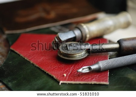 Piece of leather and some tools to work it - stock photo