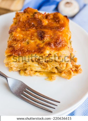 piece of meat lasagna with mushrooms on a round plate,Italian cuisine