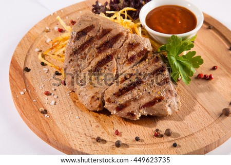 piece of meat with sauce and pepper on white background