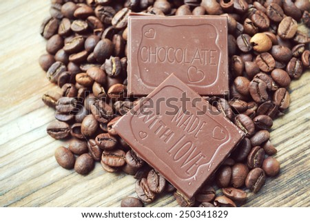 Piece of milk chocolate on coffee beans on wooden table - stock photo