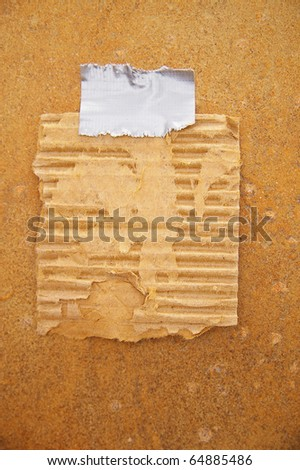 piece of old cardboard taped to a grunge wall - stock photo
