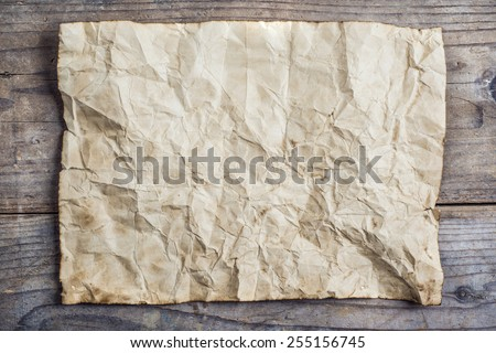 Piece of old rumpled paper on wooden floor background
