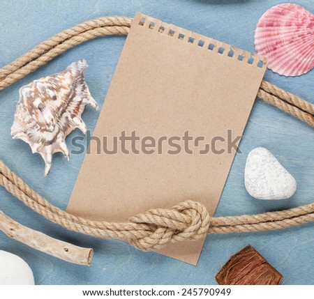 Piece of paper and sea stuff on wooden background - stock photo