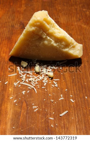 Piece of Parmesan cheese on wooden table close-up - stock photo