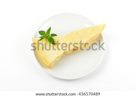 Piece of Parmesan cheese (Parmigiano Reggiano) on white plate