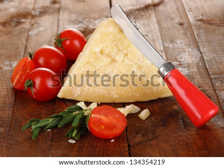 Piece of Parmesan cheese with knife on wooden table close-up - stock photo