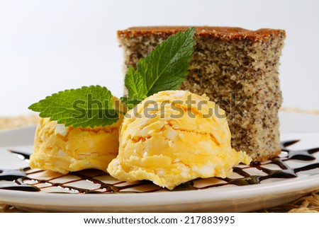 Piece of poppy seed cake with scoops of ice cream - stock photo