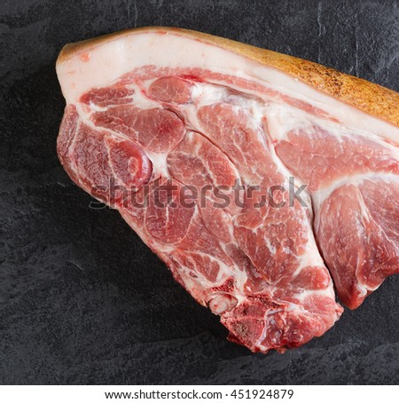 Piece of pork meat on the black stone table