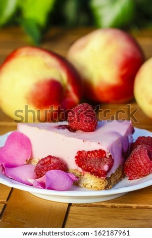 Piece of raspberry cake decorated with fresh fruits and rose petals. Romantic setting. Selective focus - stock photo