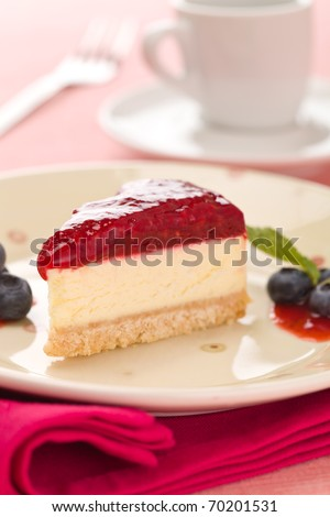 Piece of raspberry cheese cake in a plate with  fork and coffee cup in the background. Extremely shallow depth of field. - stock photo