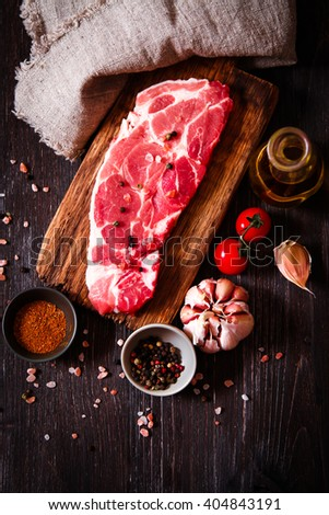 piece of raw meat beef on a wooden board with pepper dark wooden background - stock photo
