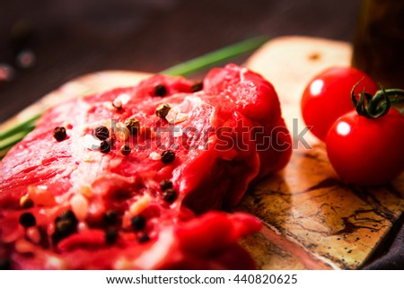 piece of raw meat with herbs and olive oil on a wooden background - stock photo