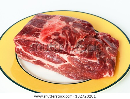 Piece of raw pork on a plate - stock photo
