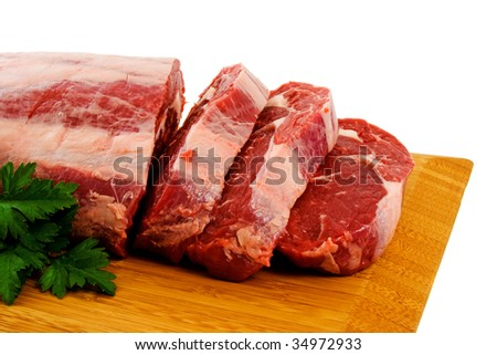 Piece of Raw Scotch Fillet being cut into steaks. - stock photo