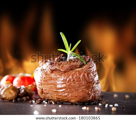 Piece of red meat steak with rosemary served on black stone surface. Blur fire flames on background - stock photo