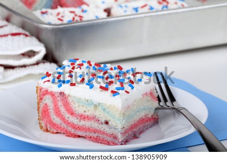 Piece of red white and blue cake on a plate Slice of cake with white icing and red and blue sprinkles