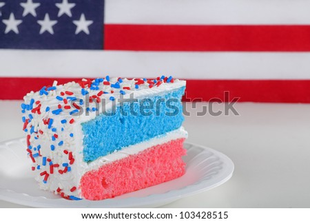 Piece of red white and blue cake with american flag in background - stock photo