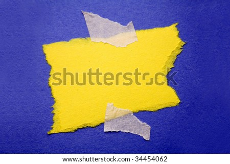 Piece of ripped paper taped to blue background