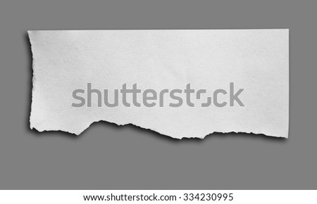 piece of ripped white paper on gray background with clipping path.