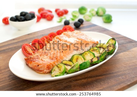 Piece of roasted salmon fillet with grilled brussels cabbage and tomatoes. Indoors still-life. - stock photo