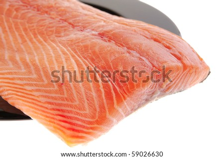 piece of salmon fillet on black plate over white