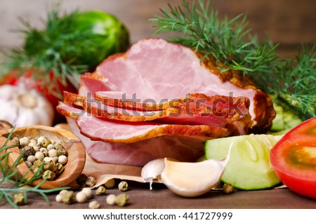 Piece of smoked meat with vegetables on a wooden background. Selective focus.