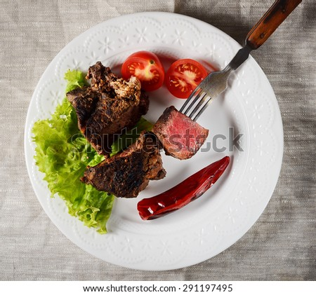 piece of steak on a fork, salad and vegetables - stock photo