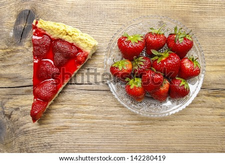 Piece of strawberry tart and fresh raw strawberries on wooden table. - stock photo