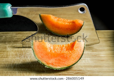 piece of succulent Orange melon rests on the Board with an axe - stock photo