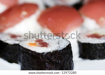 Piece of sushi with dices of tuna on the packground - stock photo
